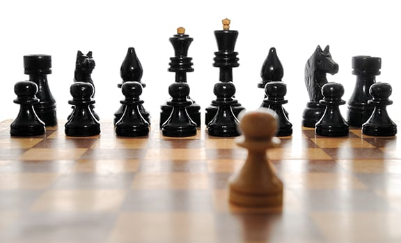 Struggle of One white pawn and black chessmen with its full complement.